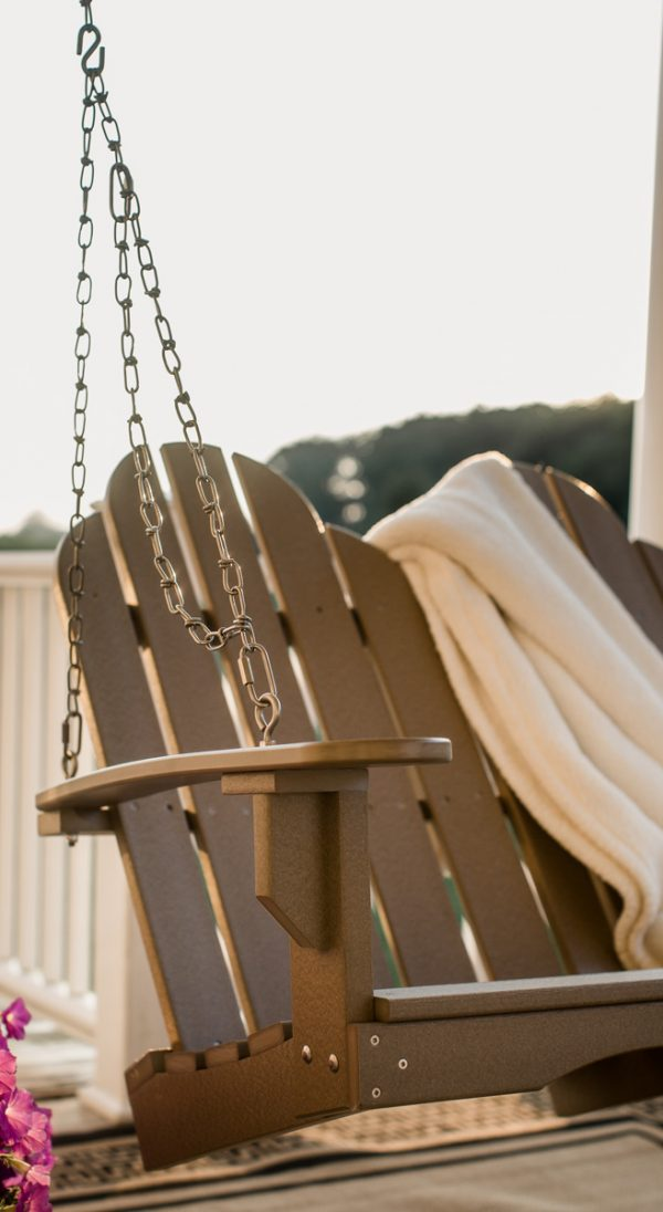 Brown Hanging Wooden Porch Swing with a Blanket Draped Over It