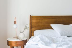 wooden bed and nightstand with lamp