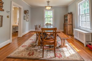Brown Wooden Dining Table on Red and White Floral Area Rug