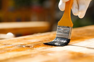 applying wood stain with brush